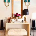 stylish turquoise shaded wall lamps flanking wooden framed wall mirror on creamy vanity with bench with furry skin cover