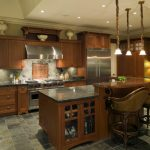 two-tier-kitchen-Island-with-Glass-Faced-Cabinetry-in-dark-hued-tones-with-dark-floor-tiling-and-matcing-toned-granite-countertops-with-rich-wood-cabinetry
