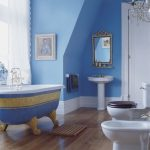 unique blue painted for bathroom color trend with unique golden accent on the bathtub with vintage wall mirror and wooden floor