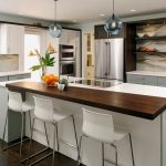 wenge kitchen fashion trend with extended wooden bar design with white stools beneath crystal pendants on wooden floor with glass window