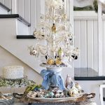 White Miniature Tabletop Christmas Tree With White Ribbon And Glossy Ornaments Sit On Table Top Near White Cake And Near The Stairs