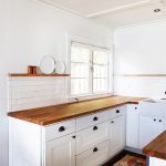 white kitchen cabinet with wooden top and floral patterned rug and mat and glass window