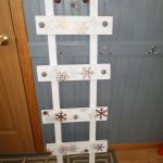 white-wood-christmas-stocking-holder-stand-from-a-unique-rustic-ladder-with-gold-and-silver-snowflakes-painting-with-5-silver-knobs-for-stockings-to-hang