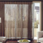 wide window treatments with attractive brown curtain and white sofs plus standing lamp and wooden coffee table