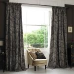 wide window treatments with black patterned curtain and leather tufted  armchair plus wooden end table with table lamp