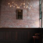 Wooden Light Fixtures With Plenty Of Bulbs Together With Brick Wall Pattern And Wooden Floor
