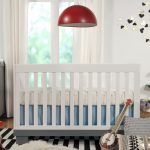 Baby crib in white by Letto Hudson a pendant lamp with red lampshade green wood tree shaped bookshelf monochromatic stripes rug for bedroom