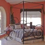 Black Iron Canopy Bed Frame In Bedroom With Red Wall Color