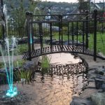 Black finished metal garden bridge idea over small artificial stream