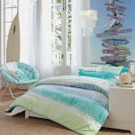 Coastal bedroom decor idea with beautiful bed comforter set a cozy chair in round shape and x base metal legs cool wall art a built in white bedside table a white surfing board white lace window drapery