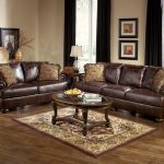 Dark Brown Leather Couch And Loveseat Sets With Stylish Pillows Wooden Glass Top Table And Decorative Rug On Hardwood Floor