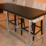 Dark finished wood counter table top idea with lightweight metal legs a pair of white upholstered bar stools