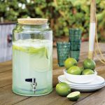Drink Dispenser With Metal Spigo And Green Lemon With White Plates