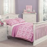 Full size bed frame with footboard and headboard for toddler flower bed comforter set in pink white bedside table with small white table lamp white storage
