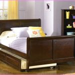 Full sized Sleigh bed frame with less curved wood headboard and footboard and also trundle addition