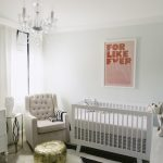 Pretty white baby crib by Letto Hudson a nursery chair in white gold colored round Ottoman table monochromatic area rug in stripe motif white shag area for bedroom