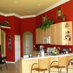 Red paint for kitchen wall with white baseboard white kitchen countertop cream schemed kitchen cabinets white kitchen door idea natural brown bar stools