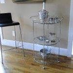 Simple and elegant round glass bar cart design with tiny metal frame and construction plus small casters