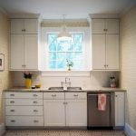 Single pendant lamp in white over the kitchen sink a pair of simple wall kitchen cabinet systems in white white kitchen cabinet underneath a pair of recessed lamps for kitchen