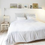 White minimalist wood shelf above the bed headboardless bed frame with stripped bed comforter set a wooden chair in shabby white washed scheme