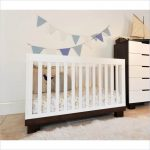 white baby crib with dark base designed by Letto Hudson