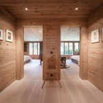 Coridor Of Home With Wood Wall And Wood Ceiling Planks Decorated With Frames And Lamps