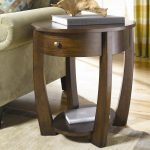 Elegant Round Wooden Small End Table With Drawer Next To Green Chair