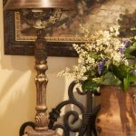 Rustic Gold Lamp With Fabric Cord Covers Flower And Vase Plus Frame On Wall