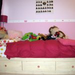 Simple Wooden Twin Bed With Drawers Underneath And Dotted Mattress Plue Red Blanket