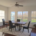 Wood Table With Black Chairs In DIning Room White Windows And Shaders Hardwood Floor Covered By Decorative Rug