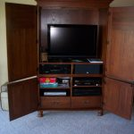 Wooden TV Hutch With Doors And Drawers On Grey Carpet
