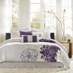 A bedding set with purple flower motif and less gray decorative motifs white fluffy area rug modern wood side table in modern style