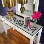 A modern console table IKEA with glass tabletop large gold schemed table lamp