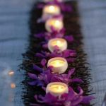 A string of candle centerpiece idea for table consisting of fresh purple flowers green grass and well organized candlesticks