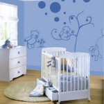 Creative and unique nursery room decor theme in blue a white baby crib with casters round white area rug a white storage unit