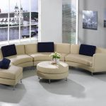 Half circle couch in cream with dark blue throw pillows a round cream cushioned center table with metal legs