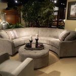 Half circle couch in gray round cushioned center table with a candle centerpiece