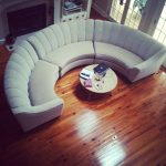 Half circle couch in white round center table made of solid wood