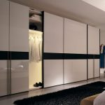 Large white sliding closet door with dark horizontal strip as the garnish