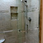 Larger standup shower idea with frameless glass door and wall mounted showerhead and handheld showerhead built ini shower shelves