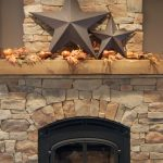 Reclaimed wood mantel decoration over modern fireplace framed with wrought iron