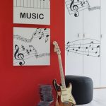 Red black and white music themed room decorating idea black bean chair a guitar and a pile of DVDs