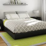 Standard size South Shore bed frame with black finish a pair of black finished wood side tables white framed yellow rug single floating shelf over bed