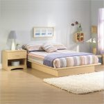 Unfinished wooden South Shore in standard size an unfinished wooden bedside table smaller fluffy white bedroom rug