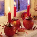 Unique And Creative Candle Centerpiece For Table Which Is Made By Putting Small And Lower Profile Candlestick Holder Over Red Apples