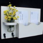 Wall mounted mail organizer idea with decorative glass vase and fresh flowers