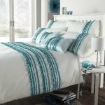 White bedding set with turquoise strips decoration in standard size bed with white wood headboard gray fluffy bedroom rug round white bedside table