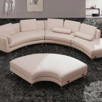 White half circle couch with white back pads a very large fluffy gray area rug for living room