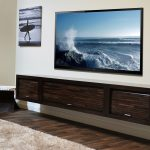 Wood floating media shelves design idea in black finishing a large flat TV set mounted on wall