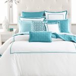 white comforter with decorative turquoise lines white and turquoise shams a queen size bed frame with tufted upholstery headboard